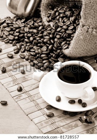 cup of coffee and roasted beans in sack burlap - stock photo