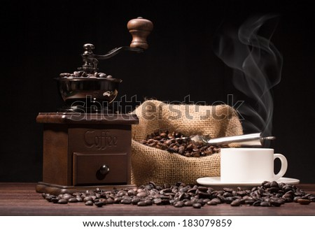 cup of coffee and roasted coffee beans with coffee grinder on black background - stock photo