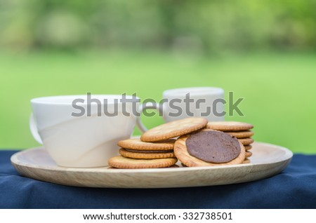 cup of coffee and sandwich-biscuit with chocolate - stock photo
