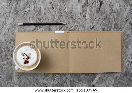 Cup of coffee and sketchbook on a wooden table - stock photo