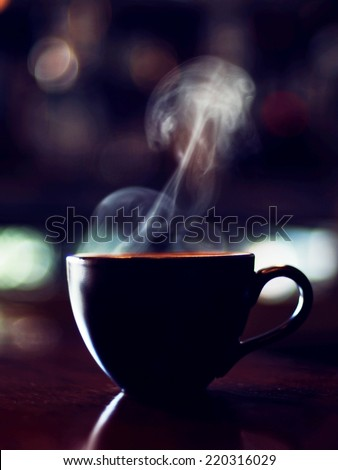 cup of coffee and smoke in vintage color tone style  - stock photo