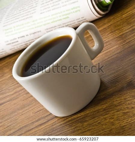 cup of coffee and stack of newspapers closeup - stock photo