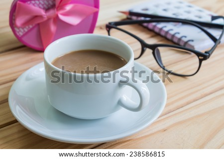 Cup of coffee and stationary on wooden table