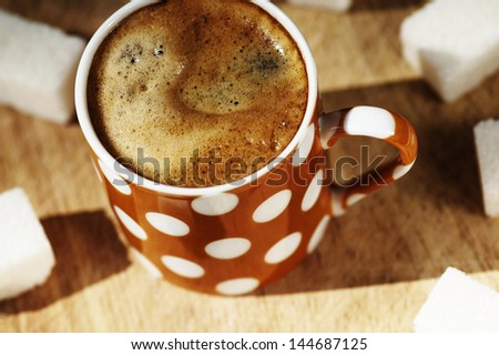 Cup of coffee and sugar cubes on wooden board top view - stock photo