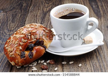 Cup of coffee and sweet buns with sunflower seeds and raisins on wooden table