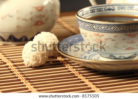 Cup of coffee and sweet on a wooden napkin - stock photo