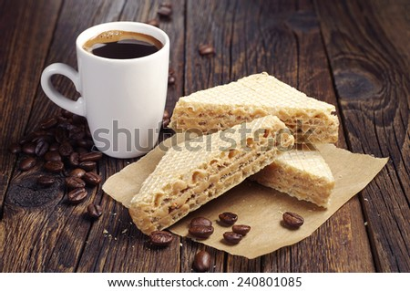 Cup of coffee and sweet waffles with condensed milk on dark wooden table - stock photo
