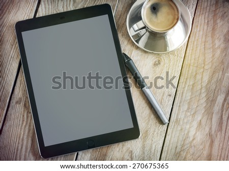 Cup of coffee and tablet on wooden table