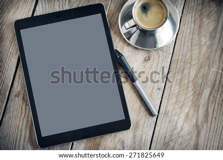 Cup of coffee and tablet on wooden table.