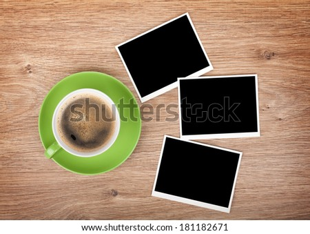 Cup of coffee and three photo frames on wooden table
