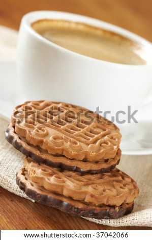 Cup of coffee and two cookies on linen napkin.