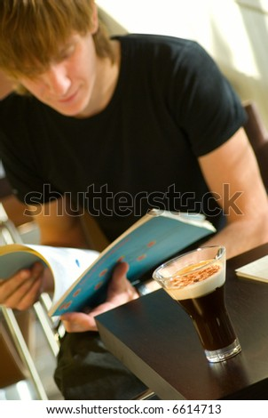 Cup of coffee and young man studying a magazine - stock photo