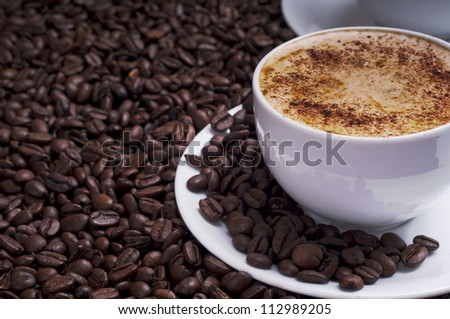Cup of coffee arranged with  fresh roasted coffee beans - stock photo