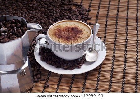 Cup of coffee arranged with  fresh roasted coffee beans and Italian coffee-maker on a wooden background - stock photo