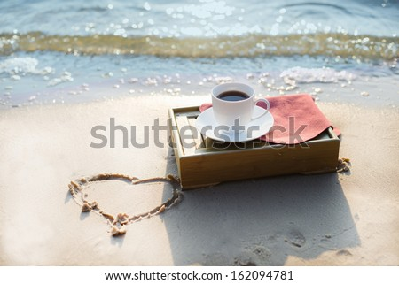 Cup of coffee at the beach - stock photo