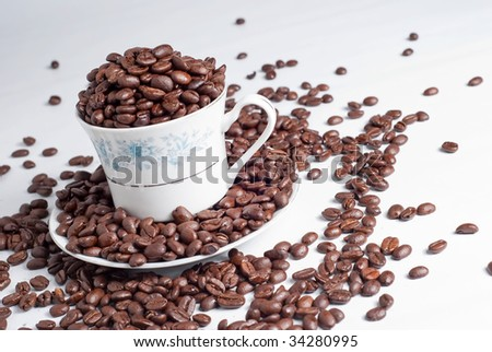 Cup of coffee beans on white background - stock photo