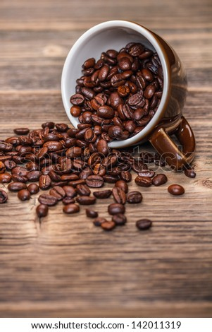 Cup of coffee beans on wooden background