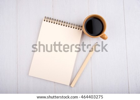 Cup of coffee, beige notebook, pencil, overhead view