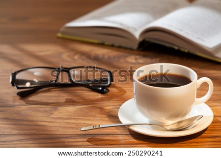 Cup of coffee, book and glasses on a wooden surface