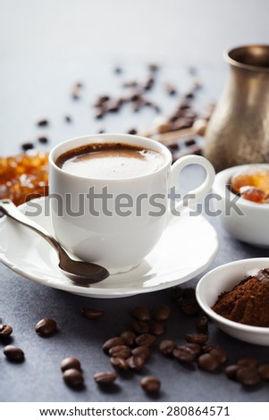 Cup of coffee, brown sugar and roasted beans on dark background, selective focus