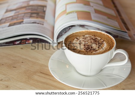 Cup of coffee cappuccino with books on table - stock photo