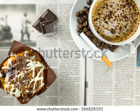 Cup of coffee, chocolate muffin and a cigarette arranged on a newspaper - stock photo