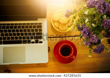 cup of coffee, cookies and laptop on wooden desk in cafe, business concept - stock photo