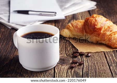 Cup of coffee, croissant and newspaper on old wooden table - stock photo
