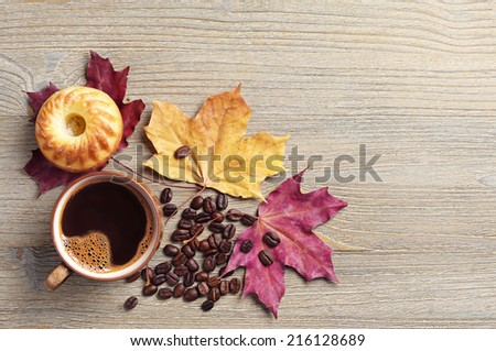 Cup of coffee, cupcake and autumn leaves on a gray wooden background. Top view - stock photo