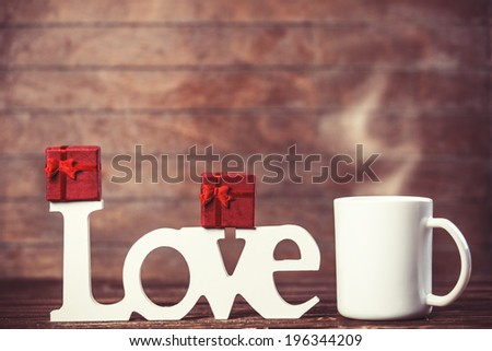 Cup of coffee, gift and word Love on wooden table. - stock photo