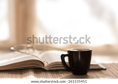 cup of coffee glasses rest on the open book against the window in the morning - stock photo