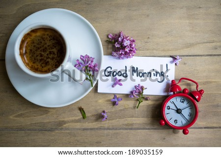 Cup of coffee, Good morning note and lilac flower on the wooden table - stock photo