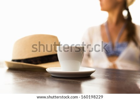 Cup of coffee, hat and woman at the background - stock photo