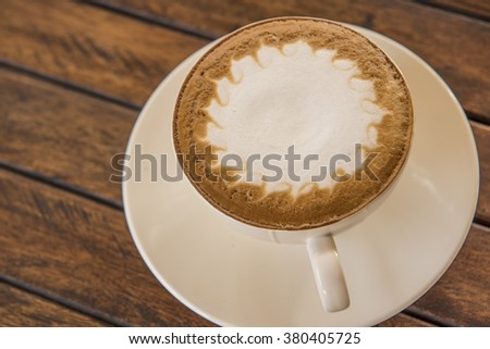Cup of coffee in a white cup on wooden background
