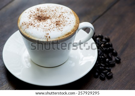 Cup of coffee in a white cup with coffee beans.
