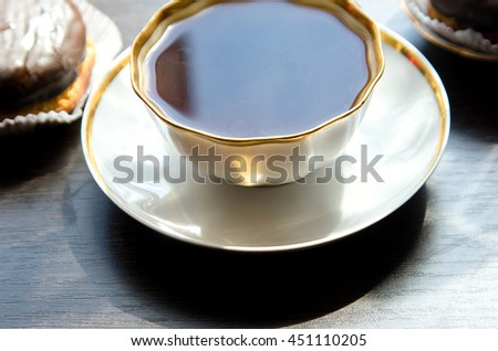 cup of coffee in a white porcelain ?up and chocolate cream puff on a dark wooden table, for calendars, illustrations - stock photo