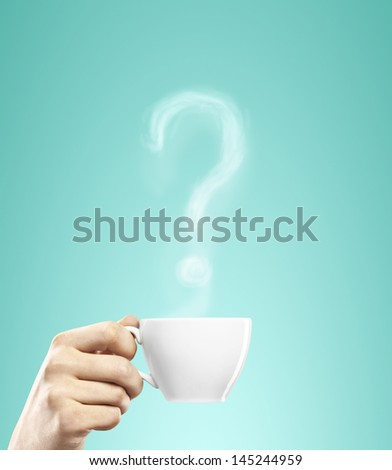 cup of coffee in hand with question mark - stock photo