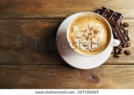 Cup of coffee latte art with grains and chocolate on wooden background - stock photo