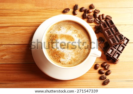 Cup of coffee latte art with grains and chocolate on wooden table, top view - stock photo