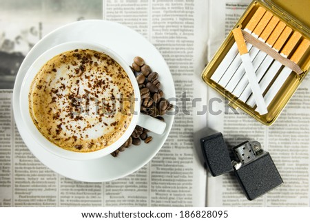 Cup of coffee, lighter and cigarettes arranged on a newspaper - stock photo
