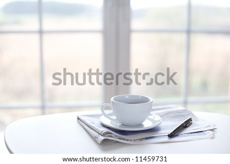 Cup of coffee, newspaper and pen on the table in front of window - stock photo