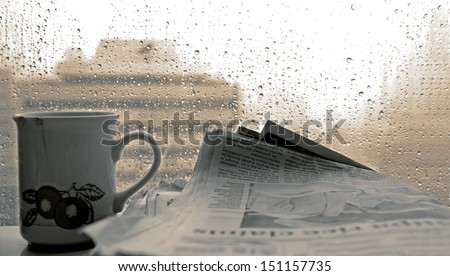 Cup of coffee,-newspaper and rain outside window - stock photo