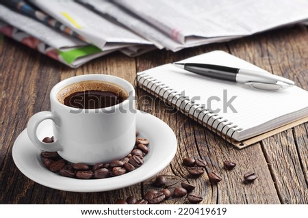 Cup of coffee, newspaper, notepad and pen on old wooden table - stock photo