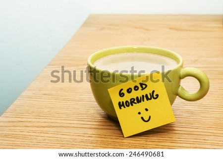 Cup of coffee, note good morning and smiley - stock photo
