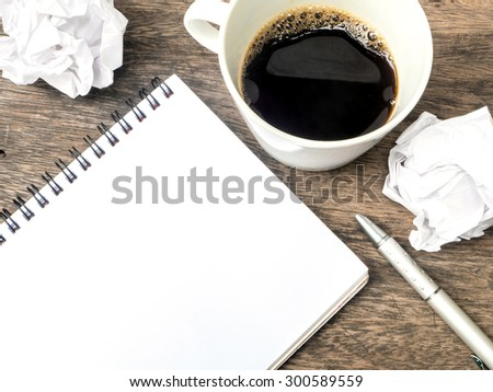 Cup of coffee , notepad and crumpled paper on wooden table - stock photo