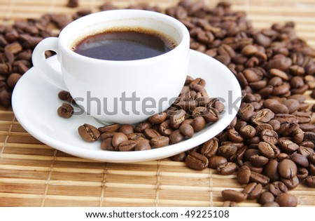 cup of coffee on a background coffee-beans and bamboo serviette