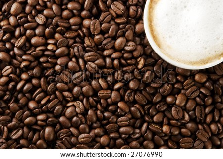 Cup of coffee on a pile of coffee beans. - stock photo