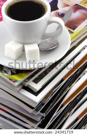 Cup of coffee on a pile of magazines. A fragment.