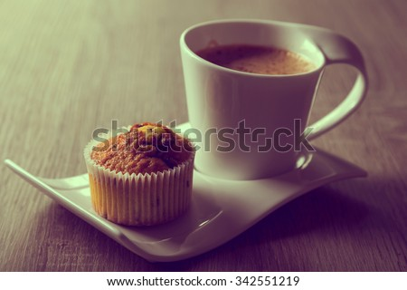 Cup of coffee on a plate next to a chocolate crunches muffin on a wooden table - stock photo