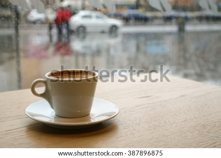 Cup of coffee on a rainy day window background - stock photo